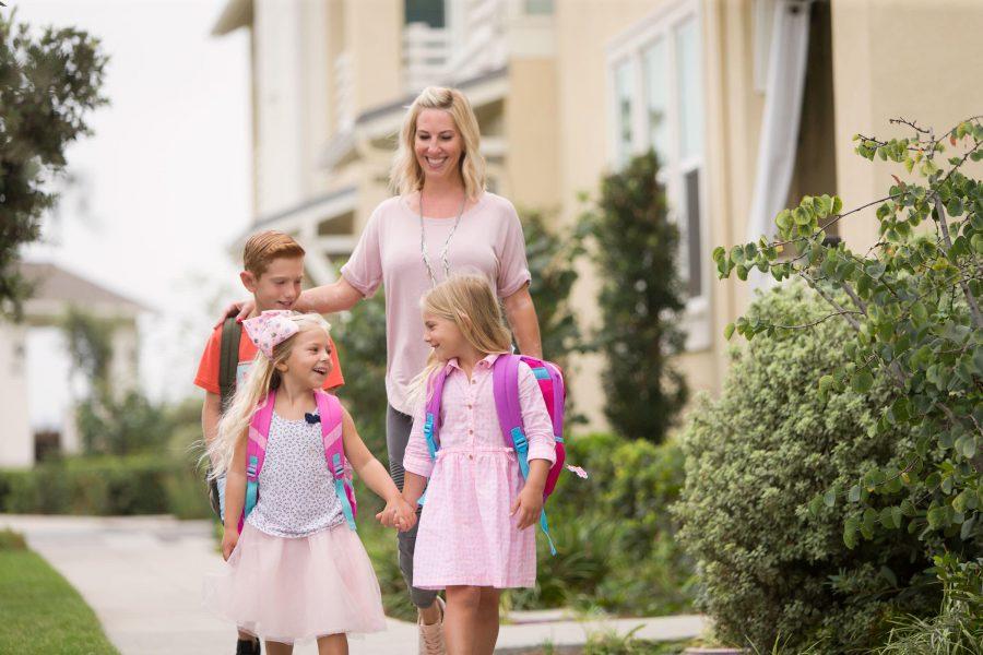 Mother walking kids to school in Esencia