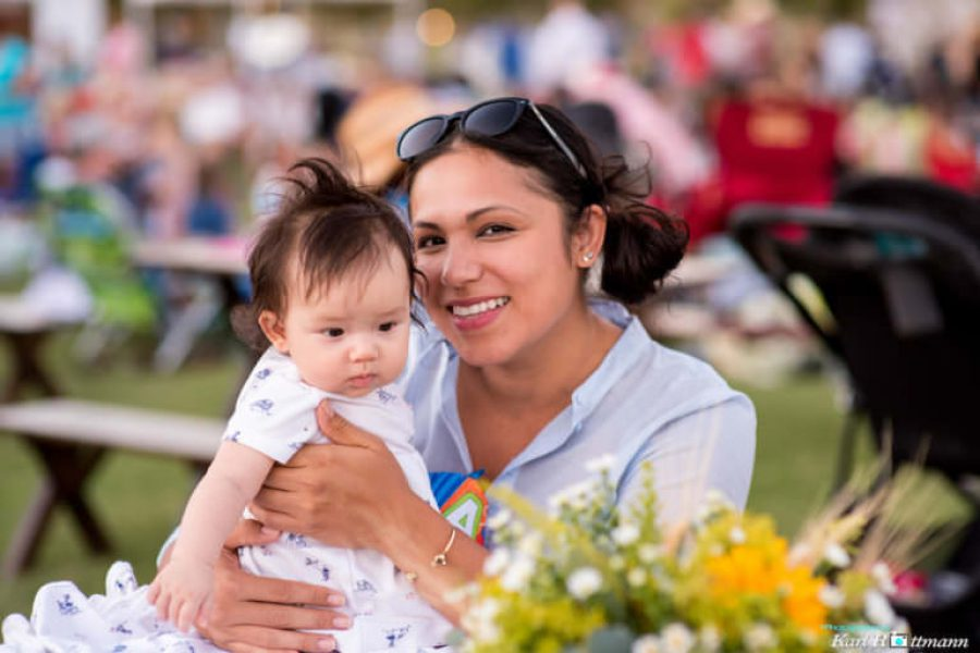WestFest woman holding baby smiling at camera